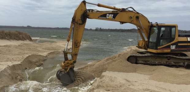 An excavator opens Sesachacha Pond to the ocean on April 12.