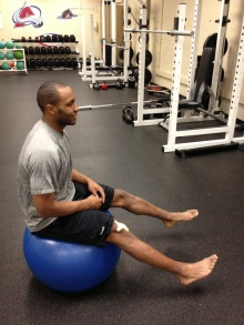 Sit on the ball without your calves touching the ball.  Balance using your core.