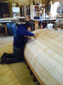 Caulking the Haven 12.5.  Photograph courtesy of Finger Boatworks.