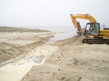 The last few bucketfulls of sand remove a berm keeping the pond at bay until the operator is ready to connect pond and ocean.