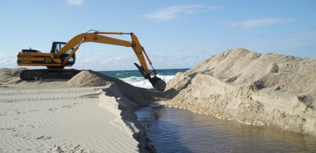 An excavator prepares to open Hummock Pond to the ocean.