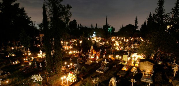 Candles and chrysanthemums on hillside graves